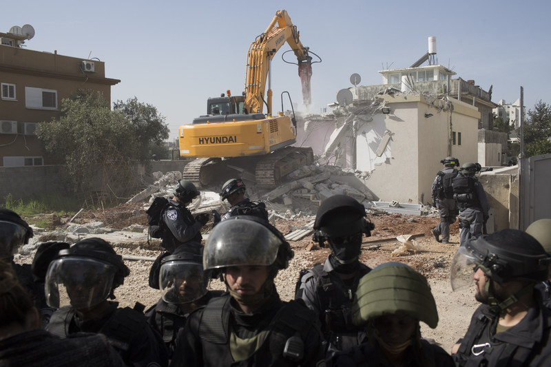Israeli authorities use a Hyundai bulldozer to destroy the home of a Palestinian citizen of Israel in the town of Lydd, Feb 10 2015. The house belonged to a single mother and her four children. (Oren Ziv, ActiveStills)