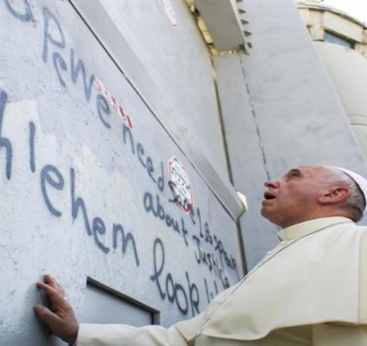 Pope Francis touches Israel's wall on his way to celebrate a mass in the Palestinian West Bank city of Bethlehem May 25, 2014